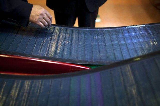 Company executives look at thin-film solar panels developed by MiaSole before a press conference held at the headquarters of Hanergy Group in Beijing, China, in 2013